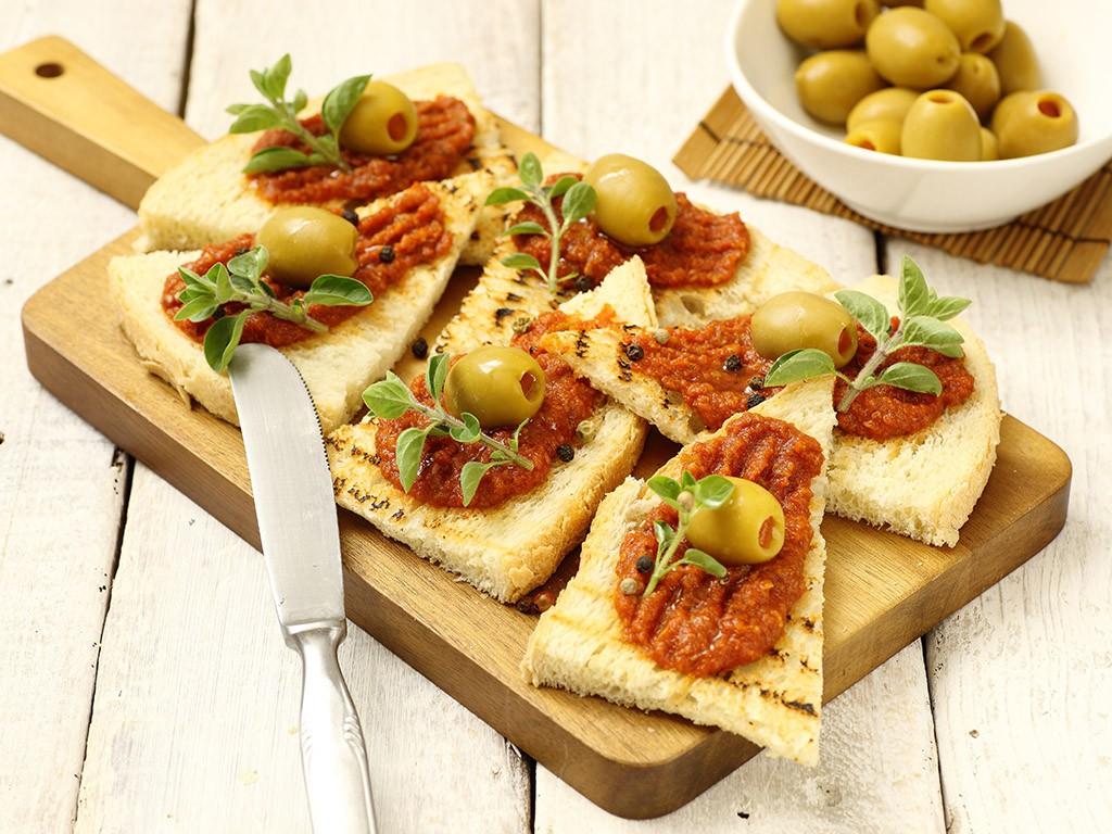 Bruschetta con Crema di Pomodoro Piccante Valfrutta Granchef, Olive verdi giganti farcite Valfrutta Granchef al peperone ed origano