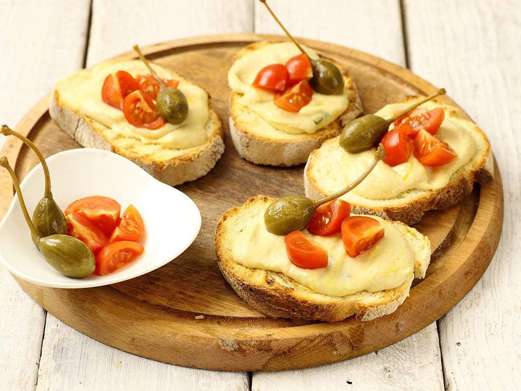 Pane lungo a fette con Crema di Ceci Valfrutta Granchef, Prezzemolo e Frutti di Cappero Valfrutta Granchef